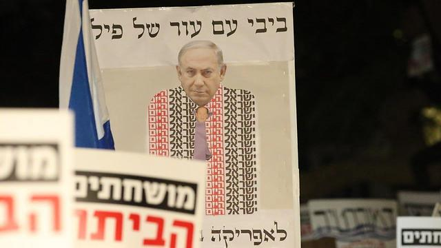 Anti Israeli government protests over alleged corruption continue PM draped in the ostensibly pro-Netanyahu newspaper Israel Hayom (Photo Moti Kimchi)